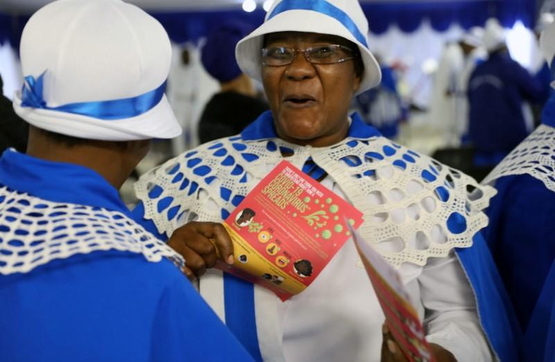 Faithful reacts as she holds a pamphlet on coronavirus disease (COVID-19) at the end of a service