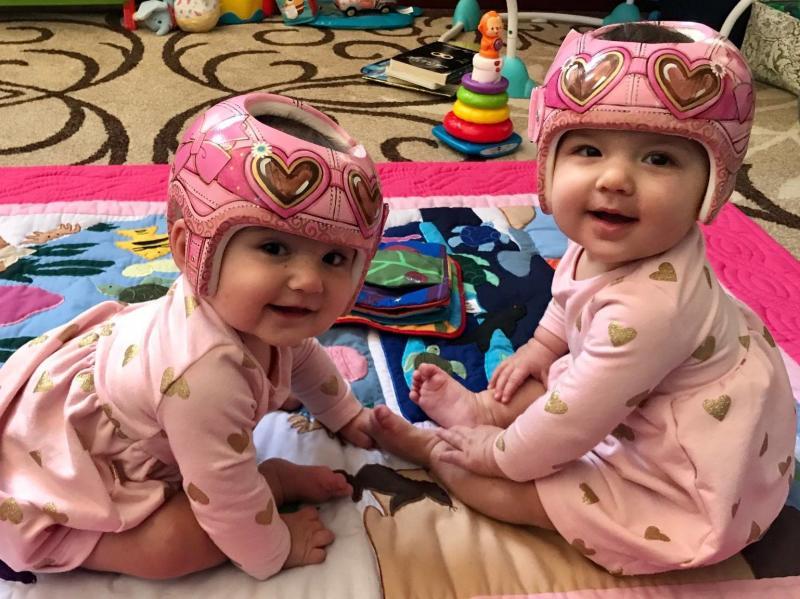 Twin baby girls wearing Lazardo designed pink helmets.