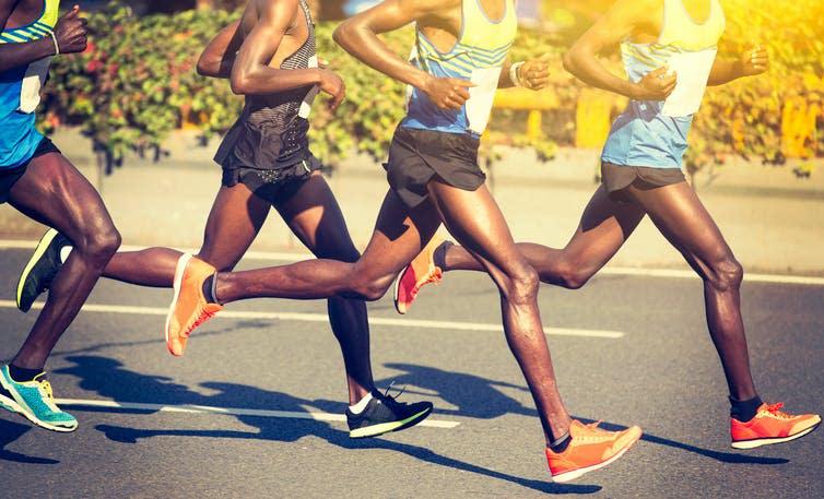 Four long-distance runners running.