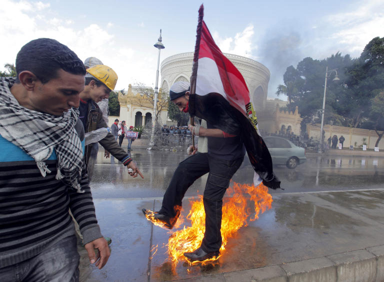 An Egyptian protester tries to escape from fire after he burned an anti-Mohammed Morsi banner in front of the presidential palace in Cairo, Egypt, Friday, Feb. 1, 2013. Thousands of Egyptians marched across the country, chanting against the rule of the Islamist President Mohammed Morsi, in a fresh wave of protests Friday, even as cracks appeared in the ranks of the opposition after its political leaders met for the first time with the rival Muslim Brotherhood. (AP Photo/Amr Nabil)