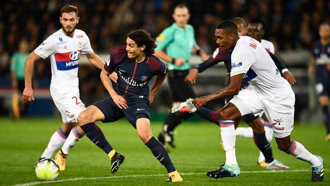 Aksi pemain PSG, Edinson Cavani melewati adangan pemain Lyon pada lanjutan Ligue 1 Prancis di Parc des Princes stadium, Paris, (17/9/2017). PSG menang 2-0. (AFP/Christhope Simon)