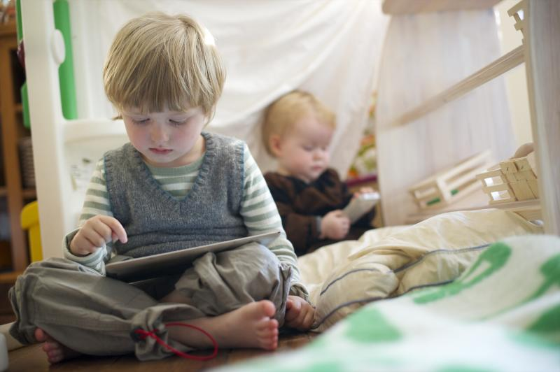 A brother, aged 4, and sister, aged 1, play with an iPad and iPhone. (Photo by Mark Makela/Corbis via Getty Images)
