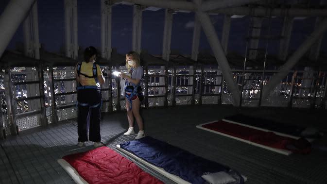 Orang-orang saat menginap di tempat berkemah semalam di atap gedung pencakar langit di Seoul, Korea Selatan (7/8/2020). Menara Lotte World membuka area berkemah jarak sosial di atap menara dan tanah untuk orang-orang yang jenuh di cuaca musim panas dan Covid-19. (AP Photo/Lee Jin-man)