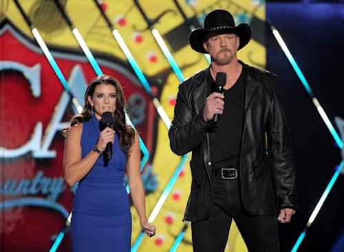 Hosts Danica Patrick, left, and Trace Adkins speak on stage at the American Country Awards at the Mandalay Bay Resort & Casino on Tuesday, Dec. 10, 2013, in Las Vegas, Nev. (Photo by Frank Micelotta/Invision/AP)