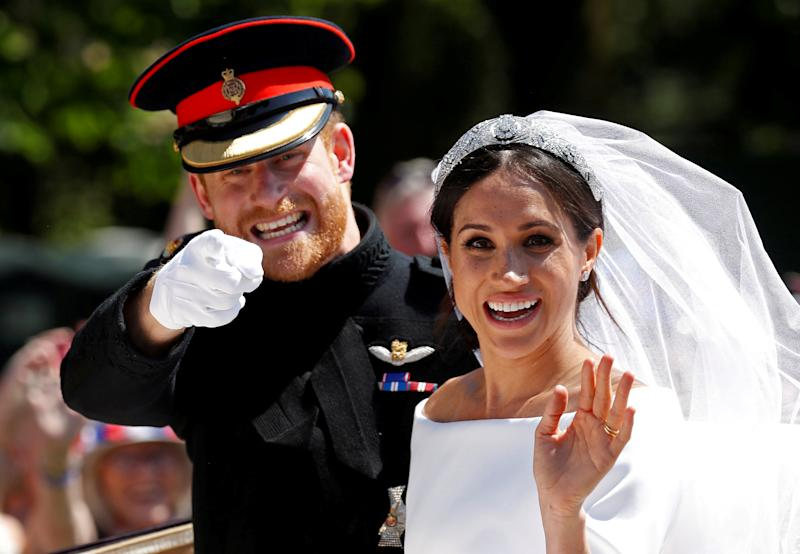 """Britain's Prince Harry gestures next to his wife Meghan as they ride a horse-drawn carriage after their wedding ceremony at St George's Chapel in Windsor Castle in Windsor, Britain, May 19, 2018. REUTERS/Damir Sagolj SEARCH """"POY GLOBAL"""" FOR FOR THIS STORY. SEARCH """"REUTERS POY"""" FOR ALL BEST OF 2018 PACKAGES. TPX IMAGES OF THE DAY."""