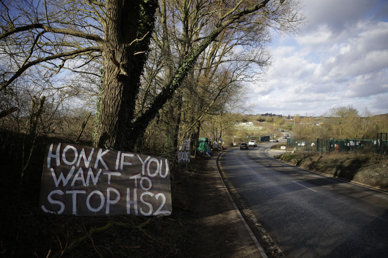 A protest sign is displayed on the roadside by a protest camp across the street from a High Speed 2 (HS2) rail line compound near the village of Harefield in north west London, Tuesday, Feb. 11, 2020. Britain's Conservative government is set to approve a contentious, expensive plan for a high-speed rail line linking London with central and northern England, despite opposition from environmentalists and even some members of the governing party. (AP Photo/Matt Dunham)