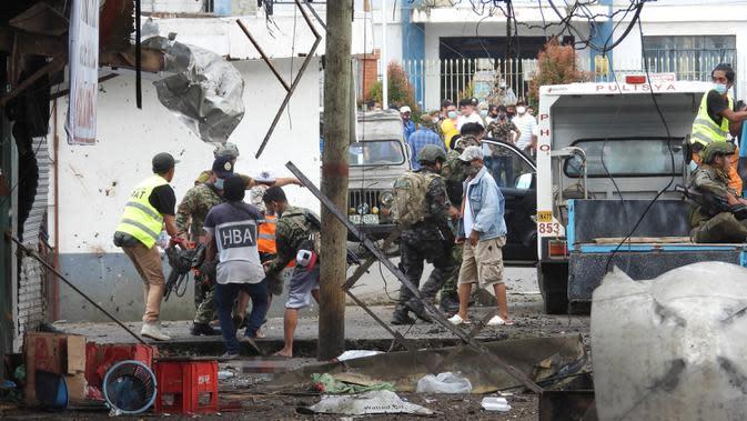 Warga dan tentara membawa tubuh korban usai bom rakitan meledak dekat kendaraan militer di Kota Jolo, Pulau Sulu, Filipina, Senin (24/8/2020). Sebanyak 10 orang tewas dan puluhan lainnya terluka -banyak dari mereka tentara atau polisi- dalam pemboman ganda tersebut. (Nickee BUTLANGAN/AFP)