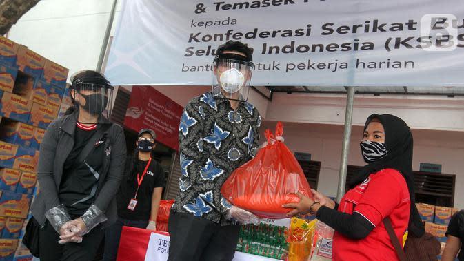 Sekretaris Pertama (Politik) Kedubes Singapura di Jakarta Matthew Chan didampingi Head of Group Strategic Marcomm PT Bank DBS Indonesia secara simbolis menyerahkan bantuan kepada pekerja harian lepas dan masyarakat terdampak COVID-19 di Jakarta. (Liputan6.com/HO/Isa)