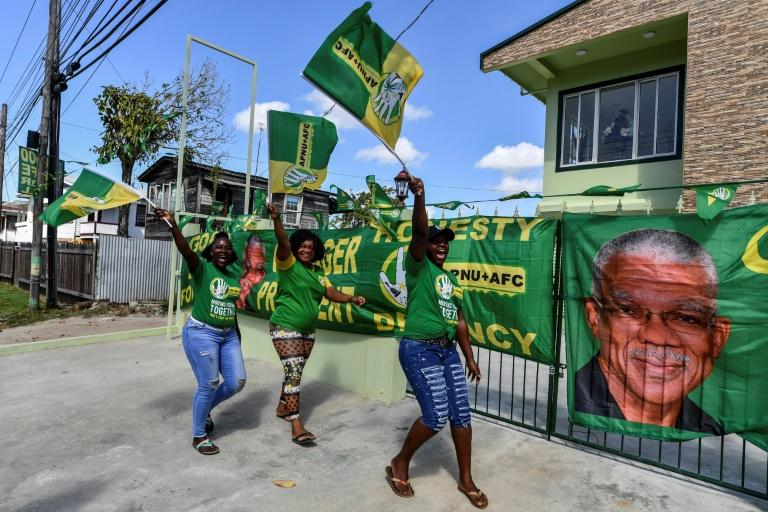 Supporters of presidential candidate David Granger cheer and wave flags in front of their house in Georgetown, Guyana, on March 1, 2020