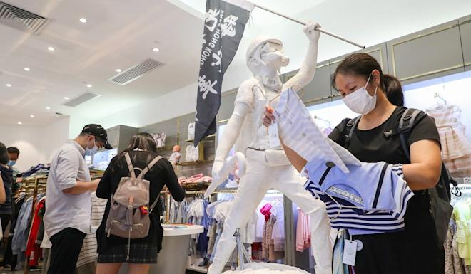 Shoppers at the Chickeeduck store at Discovery Park in Tsuen Wan look at merchandise next to the protester statue that mall management has asked be removed. Photo: Edmond So
