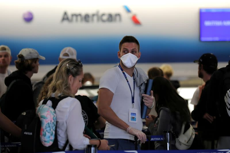 FILE PHOTO: A passenger wearing a mask waits in line to check in for a flight at Miami International Airport