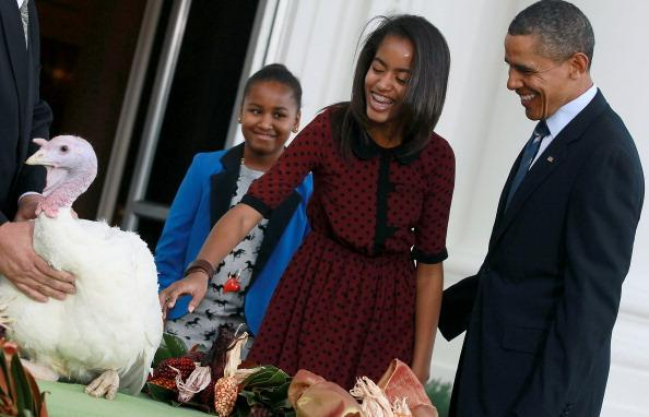 U.S. President Barack Obama is flanked by his daughters Sasha (L) and Malia (R) after pardoning 'Liberty', a 19-week old, 45-pound turkey at the North Portico of the White House November 23, 2011 in Washington, DC. The Presidential pardon of a turkey has been a long time Thanksgiving tradition that dates back to the Harry Truman administration. (Photo by Mark Wilson/Getty Images)