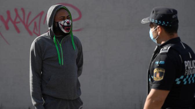 Seorang pria berbicara dengan seorang polisi ketika polisi setempat mengontrol pergerakan orang-orang di kota Fuenlabrada yang tertutup sebagian, di wilayah Madrid (22/9/2020). Pemerintah daerah Madrid telah memberlakukan penguncian sebagian di beberapa daerah berpenduduk padat. (AFP/Oscar Del Pozo)