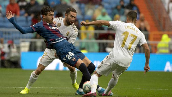 Pemain Real Madrid, Lucas Vazquez dan Isco berusaha menghentikan gelandang Levante, Jose Campana, pada laga La Liga Spanyol di Stadion Santiago Bernabeu, Madrid, Sabtu (14/9). Madrid menang 3-2 atas Levante. (AFP/Curto De La Torre)