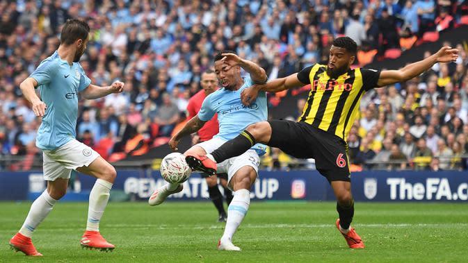 Striker Manchester City, Gabriel Jesus, berebut bola dengan bek Watford, Adrian Mariappa, pada laga final Piala FA di Stadion Wembley, London, Sabtu (18/5). City menang 6-0 atas Watford. (AFP/Daniel Leal-Olivas)
