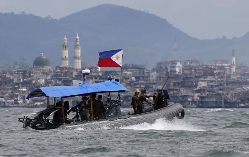 """FILE - In this Oct. 19, 2017, file photo, Philippine Navy commandos aboard a gunboat patrol the periphery of Lake Lanao as smoke rises from the """"Main Battle Area"""" where pro-Islamic group militants made a final stand amid a massive military offensive of Marawi city in southern Philippines. President Donald Trump contended this week that the United States saved the Philippines from Islamic State terrorism. His assertion vastly overstated both the threat IS posed to the country and what the U.S. did about it. (AP Photo/Bullit Marquez, File)"""