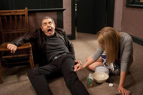 "In this film image released by Universal Pictures, Rowan Atkinson, left, and Rosamund Pike are shown in a scene from ""Johnny English Reborn"". (AP Photo/Universal Pictures, Giles Keyte)"