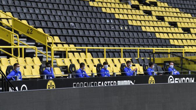 Para pemain Schalke 04 menjaga jarak ketika duduk di bangku cadangan saat bersua Borussia Dortmund pada laga pekan ke-26 Bundesliga Jerman, di Signal Iduna Park, Sabtu (16/5/2020). (AFP/Martin Meissner / POOL)