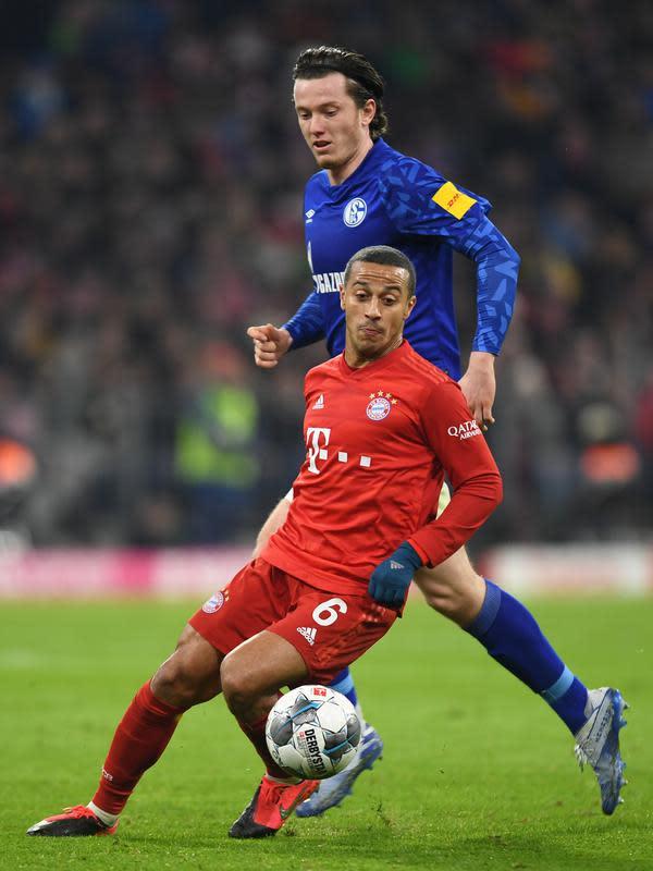Gelandang Bayern Munchen, Thiago Alcantara mengontrol bola dari kawalan pemain Schalke, Michael Gregoritsch pada pertandingan Liga Jerman di Munich pada 25 Januari 2020. Thiago akan memakai nomor punggung 6 di Liverpool. (AFP/Christof Stache)