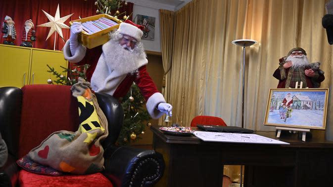 Seorang pria sebagai Father Christmas berpose saat pembukaan kantor pos Sinterklas di Himmelpfort, Jerman, Kamis (14/11/2019). Menjelang natal, Santa dan para asistennya akan berada di kantor pos untuk memastikan semua anak mendapatkan balasan surat mereka. (Tobias SCHWARZ / AFP)