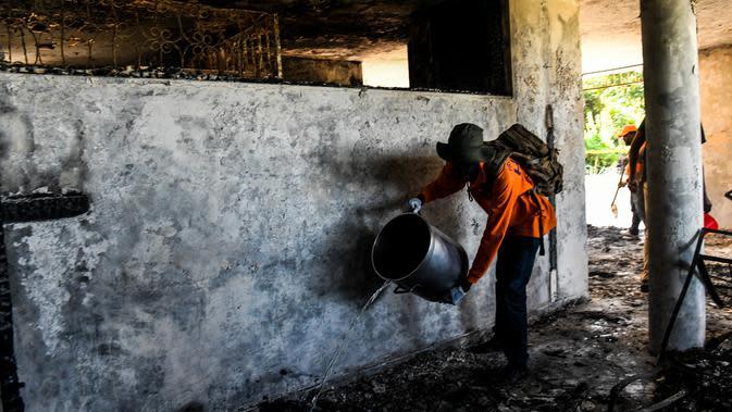 Seorang petugas pemadam kebakaran memadamkan sisa api di dalam Panti Asuhan Church of Bible Understanding, pinggiran Port-au-Prince di ibu kota Haiti, Jumat (14/2/2020). Panti asuhan yang sudah tidak berizin sejak 2013 itu menampung sekitar 66 anak-anak. (CHANDAN KHANNA/AFP)