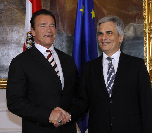 Austrian Chancellor Werner Faymann, right, welcomes American actor and former Californian Governor Arnold Schwarzenegger, left, at the federal chancellery in Vienna, Austria, Wednesday, Jan. 30, 2013. (AP Photo/Ronald Zak)