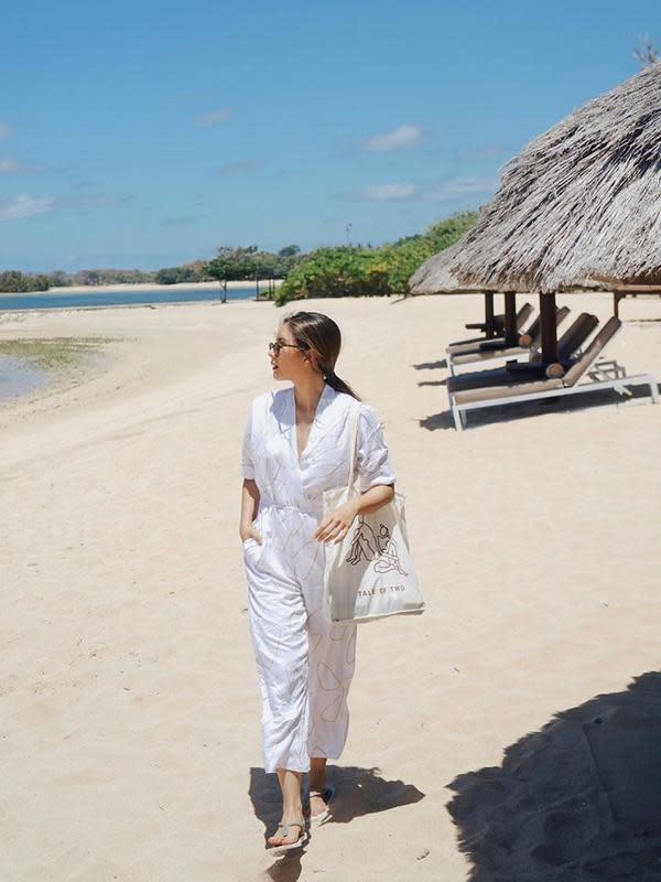 Berjalan santai di pantai, Jessica Mila nampak mengenakan pakaian bernuansa putih. Mulai dari jumpsuit, totebag, hingga sandal yang ia kenakan berwarna senada. (Liputan6.com/IG/jscmila)
