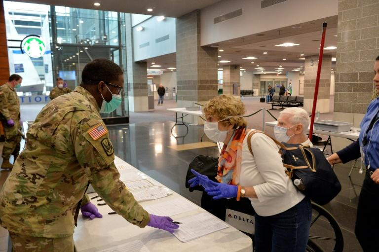A US Army National Guard soldier helps travelers register their arrival at TF Green International Airport in Warwick, Rhode Island