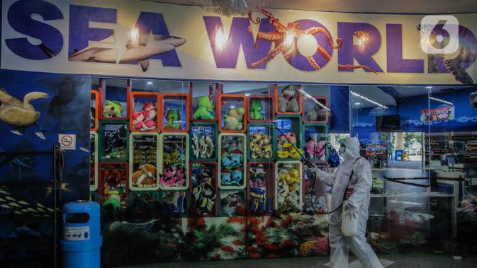 Petugas mengenakan pakaian pelindung menyemprotkan disinfektan area Sea World, Ancol, Jakarta, Sabtu (14/3/2020). Pembersihan Sea World dan Ocean Samudera guna mengantisipasi penyebaran virus corona (Covid-19). (Liputan6.com/Faizal Fanani)