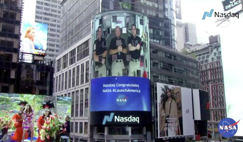 CORRECTS TO NASDAQ, NOT NEW YORK STOCK EXCHANGE - This image from video made available by NASA shows a live video of astronaut Chris Cassidy, right, ringing the opening bell of the Nasdaq Stock Exchange from the International Space Station, accompanied by fellow astronauts Robert L. Behnken, left, and Doug Hurley, broadcast on the exterior of the Nasdaq building Tuesday, June 2, 2020, in New York. (NASA via AP)