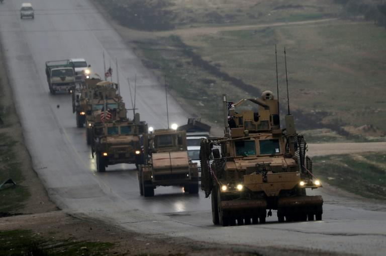 A photo taken on December 30, 2018 shows a convoy of US military vehicles driving through Syria's northern city of Manbij