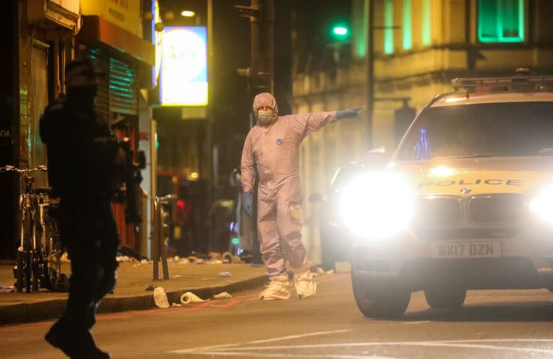 A police forensics officer gestures near the site where a man was shot by armed officers in Streatham, south London