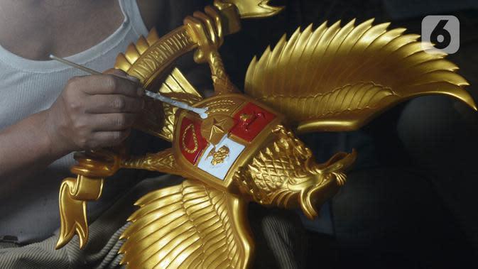 Perajin menyelesaikan kerajinan lambang Garuda Pancasila di bengkel rumahan, Jakarta, (13/8/2020). Menko bidang Perekonomian Airlangga Hartanto memaparkan anggaran Pemulihan Ekonomi Nasional (PEN) dalam bentuk bantuan bagi UMKM tercatat Rp32,5 triliun per 3 Agustus 2020. (merdeka.com/Imam Buhori)