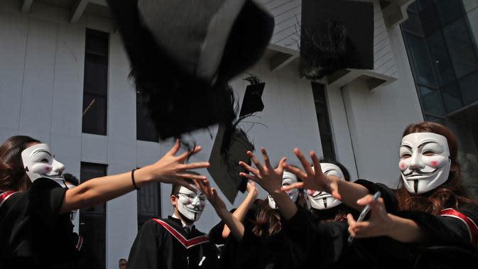 Wisudawan bertopeng Guy Fawkes melemparkan topi wisuda setelah upacara kelulusan mereka di Chinese University of Hong Kong, Hong Kong, Kamis (7/11/2019). Sekitar seribu mahasiswa mengabaikan larangan mengenakan topeng yang dikeluarkan pemerintah pada Oktober 2019. (AP/Kin Cheung)