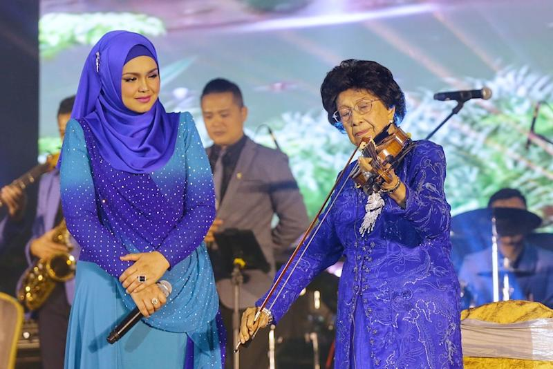 Tun Dr Siti Hasmah Mohd Ali plays the violin accompanied by Datuk Seri Siti Nurhaliza on vocals during the Warriors' Fund charity dinner at Wisma Perwira Angkatan Tentera Malaysia in Kuala Lumpur October 21, 2019. — Picture by Ahmad Zamzahuri
