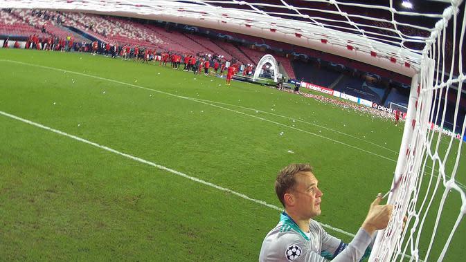 Kiper Bayern Munchen, Manuel Neuer memotong jaring gawang saat merayakan timnya meraih trofi Liga Champions usai mengalahkan PSG pada pertandingan final di stadion Luz di Lisbon (23/8/2020). Munchen menang tipis atas PSG 1-0. (AFP/Lluis Gene)