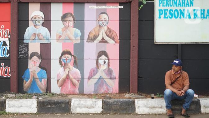 Warga duduk di dekat mural bergambar simbol orang berdoa menggunakan masker di kawasan Juanda, Kota Depok, Jumat (26/6/2020). Mural yang dibuat warga itu bertujuan memberi edukasi untuk menggunakan masker sebagai salah satu pencegahan dan penyebaran COVID-19. (Liputan6.com/Immanuel Antonius)