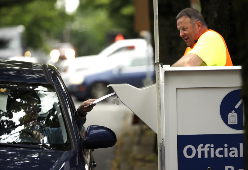 FILE - In this May 16, 2016, file photo election worker Randy Polivka watches as a motorist drops off their ballot at a ballot drop box site in Portland, Ore. The coronavirus has knocked presidential primaries back several weeks as officials worry about voters crowding into polling places. If the disease remains a hazard in November, Democrats say there's only one solution to preserve the November election, national voting by mail. (AP Photo/Don Ryan, File)