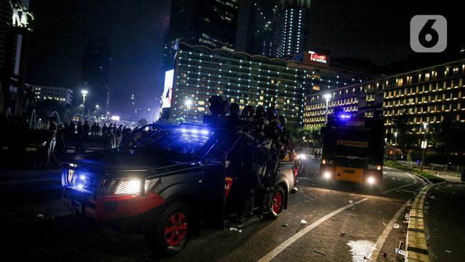 Mobil polisi lalu-lalang usai demonstrasi yang berujung anarkis di kawasan Bundaran HI, Jakarta, Kamis (8/10/2020). Massa membakar sejumlah barang saat demonstrasi menolak pengesahan UU Cipta Kerja. (Liputan6.com/Faizal Fanani)