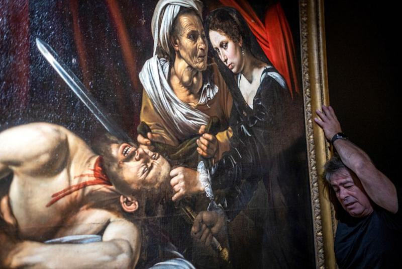 """A technician works on the hanging of a painting believed by some experts to be Caravaggio's """"Judith Beheading Holofernes"""" for its public presentation at the Marc Labarbe auction house on June 16, 2019 in Toulouse before it goes under the hammer next June 27, five years after it was discovered in the attic of an old house in Toulouse. Source: Getty"""
