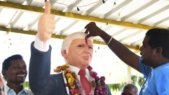 Bussa Krishna (33) memberikan tanda merah di dahi patung Presiden AS Donald Trump saat memanjatkan doa di Desa Konney, Telangana, negara bagian India selatan (14/2/2020). Trump dan istrinya Melania akan memulai kunjungan dua hari ke India. (AFP/Noah Seelam)
