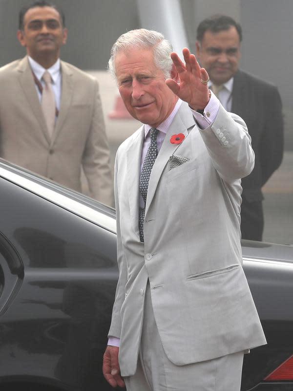 Pangeran Charles melambaikan tangan ke arah awak media setibanya bersama sang istri, Camilla di New Delhi yang diselimuti kabut asap, Rabu (8/11). (AP Photo/Manish Swarup)