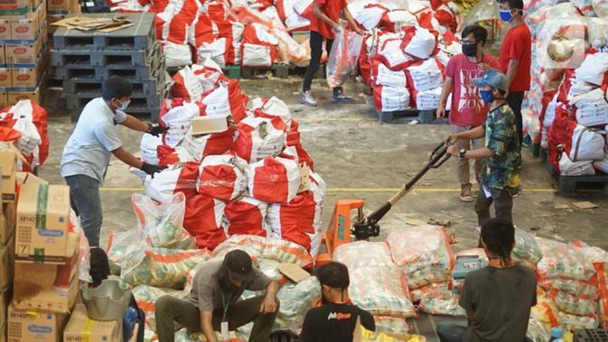 Pekerja memindahkan paket bansos di Gudang Food Station Cipinang, Jakarta, Rabu (22/4/2020). Pemerintah menyalurkan paket bansos sebesar Rp 600 ribu per bulan selama tiga bulan untuk mencegah warga mudik dan meningkatkan daya beli selama masa pandemi COVID-19. (Liputan6.com/Immanuel Antonius)