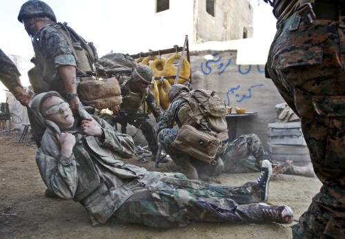 "In this Dec. 10, 2013, photo, a U.S. Navy corpsman pulls an actor to safety during a training mission at Strategic Operations where ""reality based training"" is used while working with U.S. military personnel in San Diego. (AP Photo/Lenny Ignelzi)"