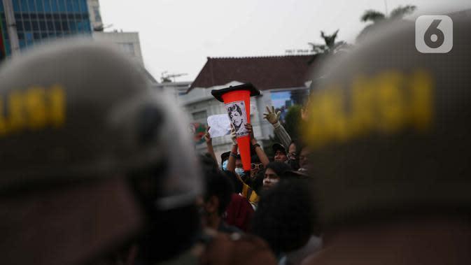 Pengunjuk rasa membawa poster bergambar almarhum Munir saat berdemonstrasi menolak UU Cipta Kerja di kawasan Harmoni, Jakarta, Kamis (8/10/2020). UU Cipta Kerja yang disahkan beberapa waktu lalu memicu demonstasi sejumlah kalangan. (Liputan6.com/Faizal Fanani)