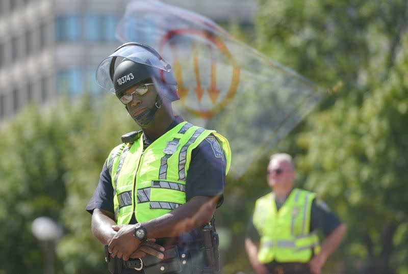 FILE PHOTO: Flag, bearing a leftist symbol associated with Antifa, is reflected behind a Boston Police officer during the Straight Pride Parade rally in Boston