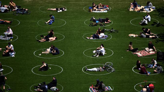 WARGA NEW YORK BERJEMUR: Orang-orang berusaha menjaga jarak dalam lingkaran putih saat bersantai di Domino Park, Brooklyn di Kota New York, Minggu (17/5/2020). Pengunjung taman berjemur dengan tetap menerapkan protokol penularan coorna Covid-19. (Photo by Johannes EISELE / AFP)