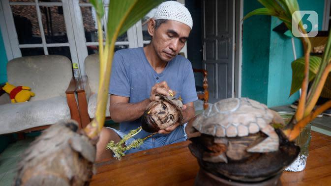 Seniman, Herman Ronda (49) mengukir bibit pohon kelapa yang dijadikan bonsai di Pondok Benda Pamulang, Tangerang Selatan, Selasa (13/10/2020). Budidaya bonsai tanaman kelapa semakin digemari untuk memanfaatkan waktu dengan harga mulai dari Rp 250 ribu hingga Rp 500 ribu. (merdeka.com/Dwi Narwoko)
