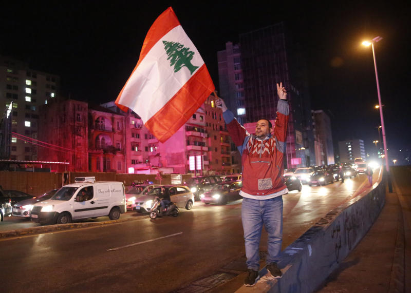 An anti-government protester flashes the victory sign and waves a Lebanese flag, as other protesters block a main road during ongoing protests against the ruling elite of corruption and financial crisis, in Beirut, Lebanon, Monday, Jan. 13, 2020. Lebanon is facing its worst economic crisis in decades, while protests against corruption and mismanagement have gripped the country since October. (AP Photo/Hussein Malla)