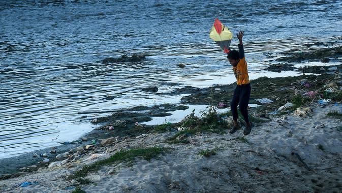 Seorang anak menerbangkan layang-layang di tepi sungai menjelang festival Hindu Dashain di Kathmandu (7/10/2020). Festival ini yang paling dinantikan di Nepal, Bhutan, Burma, dan perbukitan India Utara. (AFP/Prakash Mathema)